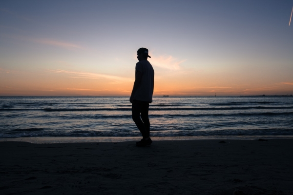 man standing on beach shore during daytime