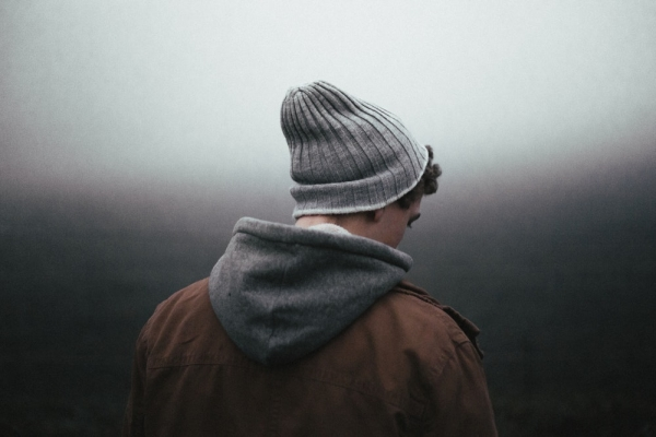 man wearing knit cap on grey background