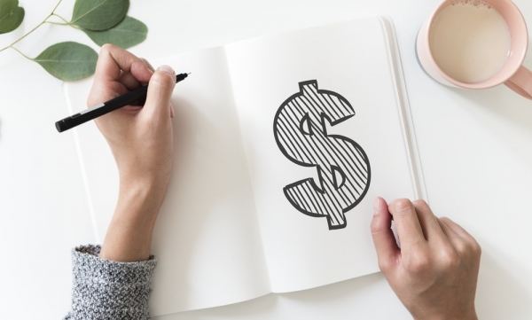 person writing dollar sign on sketch book