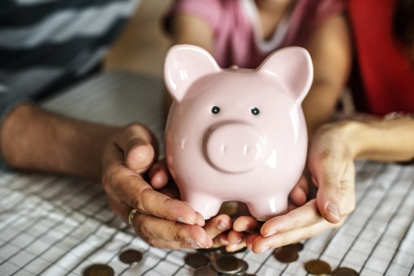 person holding pink ceramic pig coin bank